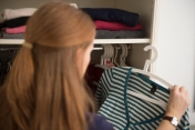 Woman_looking_through_clothes_in_wardrobe